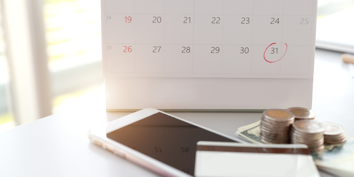 Table with phone, card, money and a calendar with the date circled